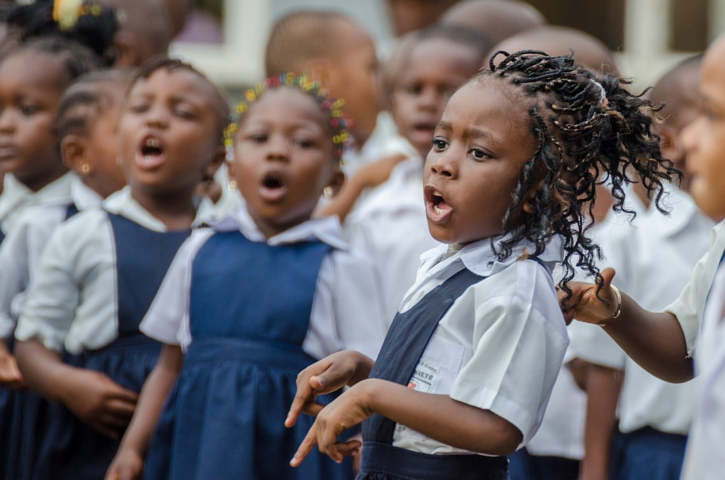 Young African school girl with beautifully decorated hair singing and dancing at pre-school in Matadi, Congo, Africa